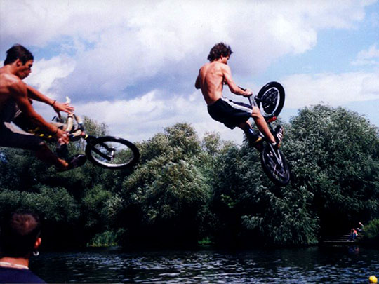 Jumping into a river with bike